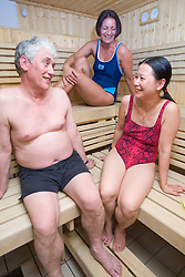 Adults relaxing in the sauna at their sports leisure centre,