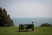 An elderly couple sit on a wooden bench and talk looking out at the English Channel on The Leas Promenade, Folkestone, Kent, England, United Kingdom.  The bench is part of Christian Boltanski's The Whispers sound installation initially commissioned by Folkestone Triennial arts festival 2008.