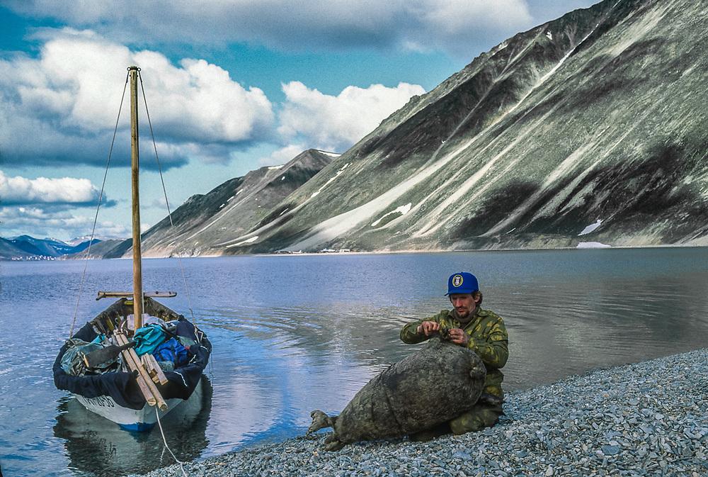 Oleg Gaifullin, Russian guide, repairs a seal skin float, Plover Spit near the Port Town of Provideniya, Chukotsk Peninsula, NE Russia, 1992