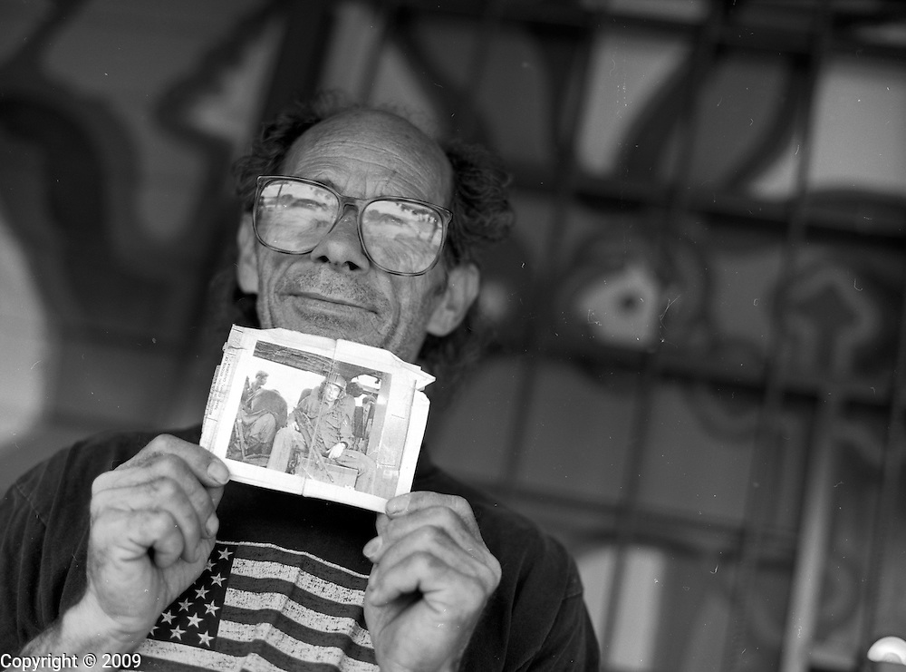 In 2003, Jerry Hogan, a Vietnam Veteran, holds a photograph of himself when he began crewing a helicopter in B Troop, 1st Squadron, 9th Cavalry at Quan Loi in III Corps during November 1969.