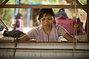 15 MARCH 2006 - CHONG KOH, KANDAL, CAMBODIA: A woman works a loom in Chong Koh, a village on the Mekong River in central Cambodia. The community is known for its weaving. Women in the community specialize in silk-cotton blends for scarves and skirts. PHOTO BY JACK KURTZ