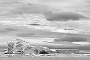 Black and white Ice berg and tabular ice beneath storm clouds at Brown Bluff, West Antarctica Peninsula, The Antarctic