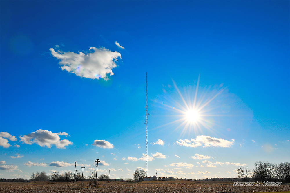 """I captured this landscape while in Rensselaer, Indiana on December 4th, 2019. When I captured this landscape, I wanted a """"sunstar"""" to be the main subject since the sky was very clear. I used the radio tower as a center point for the image as I think its an unconventional but interesting element for a landscape image. I used a circular polarizer lens filter to darken the blue sky and reduce glare from the atmosphere to make the sunstar and few clouds contrast better with the background and to make the sky more vivid.<br /> <br /> Printed on Hahnemühle German Etching paper. Limited to 100 productions per size.<br /> <br /> Framed prints are available in 18"""" x 12"""", 24"""" x 16"""", 30"""" x 20"""", 36"""" x 24"""", 45"""" x 30"""", and 60"""" x 40"""" sizes."""