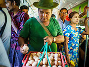 25 NOVEMBER 2017 - YANGON, MYANMAR: A man selling hard boiled eggs as a snack on the Yangon Circular Train. The Yangon Circular Train is a 45.9-kilometre (28.5 mi) 39-station two track loop system connects satellite towns and suburban areas to downtown. The train was built during the British colonial period, the second track was built in 1954. Trains currently run both directions (clockwise and counter-clockwise) around the city. The trains are the least expensive way to get across Yangon and they are very popular with Yangon's working class. About 100,000 people ride the train every day. A a ticket costs 200 Kyat (about .17¢ US) for the entire 28.5 mile loop.    PHOTO BY JACK KURTZ