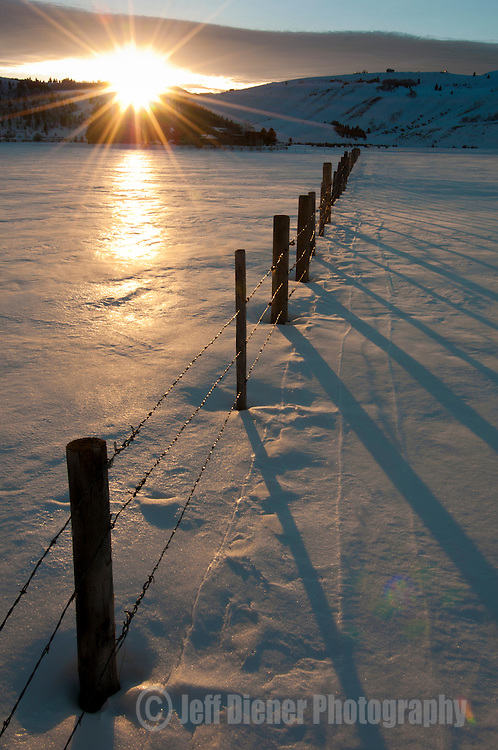 A snowy field and fenceline at sunset in  the Spring Gulch valley of Jackson Hole, Wyoming.