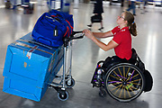 "A disabled airline passenger makes her own way through the Departures concourse of Heathrow Airport's Terminal 5. Pushing her racing wheelchair, possibly for a race in another country, the lady heads for a British Airways check-in zone before a long-haul flight to compete as a paraplegic. Pushing her possessions on an airport trolley, she speeds through the terminal showing tanned, muscular arms and a bottle of Evian mineral water. From writer Alain de Botton's book project ""A Week at the Airport: A Heathrow Diary"" (2009). ."