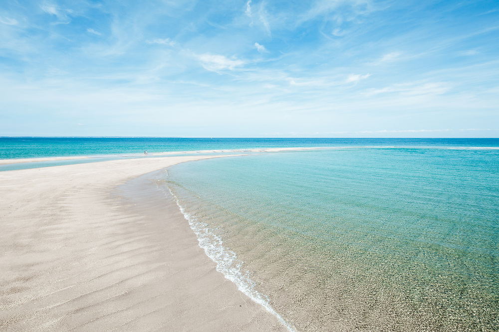 Perfectly calm, crystal clear, turquoise water surrounding the deserted sandbanks at the paradise beach location of the Minquiers, off the coast of Jersey, CI