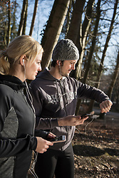 Man and woman in sportswear holding smart phone with headphones and checking the time in forest