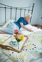 Mature man having breakfast in bed with digital tablet, smiling