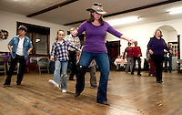"Cookie Boulanger, Mollie Durand and Kristen Durand-Schwarz join together with friends and work on  their ""Texas Two Step"" at the Wicwas Grange Hall's Spring Fling Hoedown dance Saturday evening.   (Karen Bobotas/for the Laconia Daily Sun)"