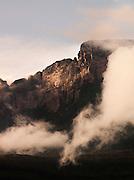 The sun illuminates the rocks of Auyantepui, home of Angel Falls, seen here from Uruyen village in Canaima National Park, Venezuela