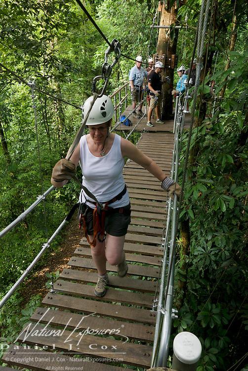 Christine Crosby crossing suspension bridge during zip line run. Costa Rica.