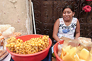 MERIDA, YUCATAN, MEXICO: A Mayan woman sells fruit on the street in Merida, capital of the Yucatan in Mexico. Merida is popular with Mexican and foreign tourists alike who visit the city to see the colonial architecture and explore the Mayan Indian communities in the area.  01 AUGUST 2003 PHOTO BY JACK KURTZ