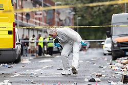 © Licensed to London News Pictures . 12/08/2018. Manchester , UK . Forensic scenes of crime examiners at the scene . Police have closed off Claremont Road in Moss Side after a shooting overnight during the annual Caribbean Carnival celebrations . Ten people are in hospital . Photo credit : Joel Goodman/LNP
