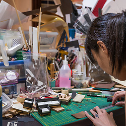 Cherry, Yean's sister (the founder of Skea which specializes in custom made paper gifts for the spirits) - in her workshop near Taipei. She's working on furniture.<br /> <br /> Buddhists believe in the neverending cycle of life, death, and reincarnation. With consumerism taking its toll on our society, interdimensional love has also been redefined. Back in the days, it sufficed to send the deceased loved ones a stack of hell money or perhaps a slip of paper with imprinted clothing (including a scissors icon in case the size doesn't fit). But nowadays it seems incredibly important to upgrade to fancier donations for the ancestral spirits, and furthermore to ensure they can keep up with technological trends in their afterlife. Thus, people buy all sorts of lavish gifts made of paper mâché to honor the dead, not necessarily for the wandering spirits, as those are already appeased with the Pudu rites hold for them during Ghost Month. Besides the funerals, biweekly Bai-Bai tributes, and individual death anniversaries, the peak season for producers to sell their 3D paper imitations is the annual Tomb Sweeping Day Qingming. <br /> <br /> Skea is distributing meaningful and eco-friendly paper products via webshop all over Asia. The product range includes luxurious mansions with swimming pools, entertainment stuff such as entire discos, ice cream parlors, sports gear, plus every means of transport imaginable – sports cars, jets, bicycles, motorbikes. Skea also offers imitated electronic gadgets such as cameras, or phones and tablets where even the apps are designed by Skea. There's watches, jewelry, razors, perfumes, sunglasses, hats, the latest fashion (formal, traditional and casual dresses) – basically everything needed to dress swag and live comfy in the afterlife.<br /> <br /> Smaller presents like the latest sPhone 8plus (with 80 GB spiritual memory) is available for about USD 100, whereas an entire villa with all the trimmings goes for about USD 4.500