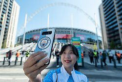 © Licensed to London News Pictures. 25/04/2021. LONDON, UK.  A City fan takes a selfie outside Wembley Stadium for the Carabao Cup final between Manchester City and Tottenham Hotspur.   8,000 spectators, comprising fans from both teams, NHS workers and local residents will watch the match which is an official test event for the UK Government's Events Research Programme.  Data will be collected for managing and mitigating Covid-19 transmission so that venues can prepare to accommodate fuller crowds and audiences as lockdown restrictions are eased.  Photo credit: Stephen Chung/LNP