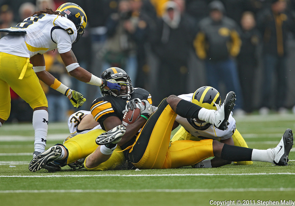 November 05, 2011: Iowa Hawkeyes wide receiver Marvin McNutt (7) hangs onto the ball as he is hit by Michigan Wolverines cornerback J.T. Floyd (8) and Michigan Wolverines safety Jordan Kovacs (32) during the second half of the NCAA football game between the Michigan Wolverines and the Iowa Hawkeyes at Kinnick Stadium in Iowa City, Iowa on Saturday, November 5, 2011. Iowa defeated Michigan 24-16.