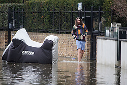 © Licensed to London News Pictures. 01/01/2018. London, UK. Residents wade through flood water covering the roads along the embankment at Chiswick in West London where the River Thames has broken it's banks. Photo credit: Ben Cawthra/LNP