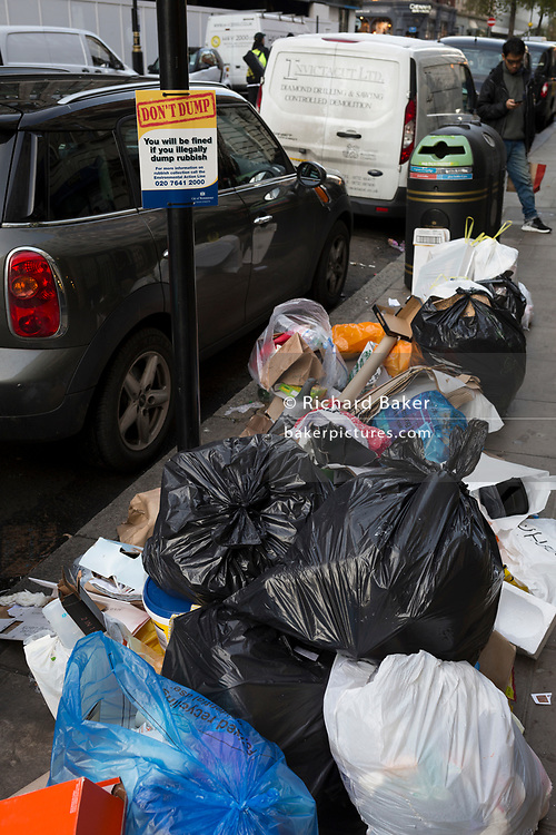 Piles of bagged garbage lies on the street beneath a warning sign for illegal dumping, resulting in fines and prosecution, on 12th December 2017, in London England.