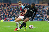 Barnsley forward Mamadou Thiam (26) holds off Burnley defender James Tarkowski (5) during the The FA Cup 3rd round match between Burnley and Barnsley at Turf Moor, Burnley, England on 5 January 2019.