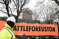 London, UK. 31 January, 2021. A HS2 security guard passes anti-HS2 activists from umbrella campaign group HS2 Rebellion hanging a 'Stop HS2 Now - Battle for Euston' banner from fencing erected by HS2 Ltd around Euston Square Gardens. Climbers from the National Eviction Team (NET) are currently dismantling a camp built by activists, five of whom still occupying tunnels beneath the camp, in order to seek to protect trees from felling by HS2 Ltd in connection with the controversial HS2 high-speed rail project.