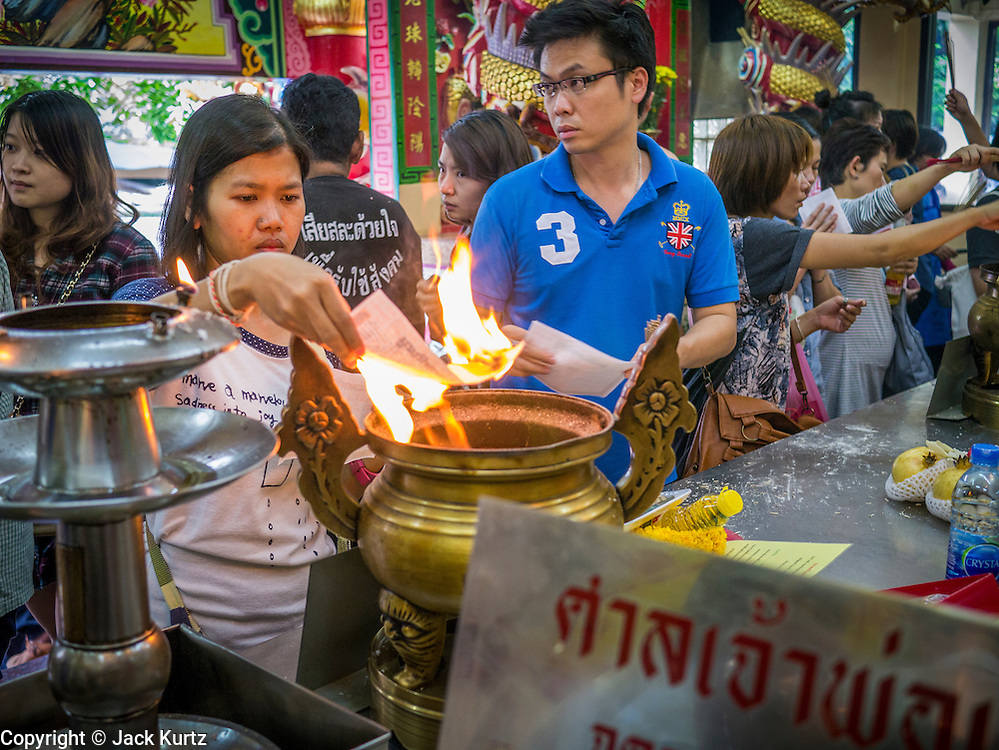 "24 FEBRUARY 2013 - BANGKOK, THAILAND: People pray and burn slips of paper after ""making merit"" by buying coffins for the indigent at the ""coffin temple"" of the Ruamkatanyu Foundation next to Wat Hua Lamphong. The Ruamkatanyu Foundation provides coffins for Bangkok's indigent and emergency medical services for accident victims in Bangkok. Wat Hua Lamphong is a Royal Buddhist temple, third class, in the Bang Rak District of Bangkok, Thailand. It is located on Rama IV Road, approximately 1 km from the city's main Hua Lamphong railway station. An entrance to Sam Yan Station on the Bangkok metro (subway) is located outside the main entrance to the temple compound on Rama IV. Wat Hua Lamphong was renovated in 1996 to mark the 50th anniversary of the ascension to the throne of King Bhumibol Adulyadej (Rama IX) in 1996. The royal seal of what became known as the Kanchanapisek, or Golden Jubilee, year, showing two elephants flanking a multi-tiered umbrella, are featured in the temple's remodeling.     PHOTO BY JACK KURTZ"