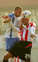 Photo: Frances Leader.<br />Brentford v Swindon Town. Coca Cola League 1.<br />15/10/2005.<br /><br />Brentford's Junior Lewis and Swindon's Andrew Gurney head the ball.