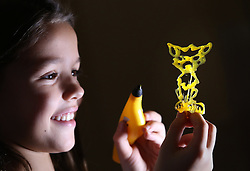 © Licensed to London News Pictures. 04/11/2015. London, UK. Valeria, 8 makes a cat figure with the 'i Do 3D' kit at the Dream Toys Christmas event. Photo credit: Peter Macdiarmid/LNP