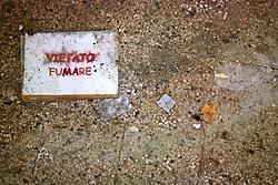 """Sporcizia di vario tipo e un """"Vietato Fumare"""" sul pavimento all'interno dei locali dell'ex centro di permanenza temporanea """"Casa Regina Pacis"""" a San foca (LE) ormai in disuso. 21/02/2010 (PH Gabriele Spedicato)..I Centri di permanenza temporanea (CPT), ora denominati Centri di identificazione ed espulsione (CIE), sono strutture istituite in ottemperanza a quanto disposto all'articolo 12 della legge Turco-Napolitano (L. 40/1998) per ospitare gli stranieri """"sottoposti a provvedimenti di espulsione e o di respingimento con accompagnamento coattivo alla frontiera"""" nel caso in cui il provvedimento non sia immediatamenti eseguibile."""