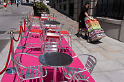 A delivery man pushes a trolley with retail supplies, past a pink carpet with silver street tables and seating which stretches uphill in Aldwych, on 23rd June 2021, in Westminster, London, England.