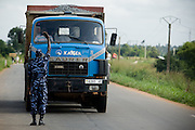 A police officer stops a truck at a checkpoint outside Lome, Togo on Thursday October 2, 2008.