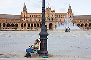 With his brush at the ready, a donkey ride owner awaits new business during the quiet Siesta afternoon period in Seville's Plaza de Espana. This semi-circular enclosure was built by Aníbal González, the great architect of Sevillian regionalism, for the Ibero-American exposition held in 1929. Today the Plaza de España mainly consists of Government buildings. The Seville Town Hall, with sensitive adaptive redesign, is located within it. The Plaza's tiled 'Alcoves of the Provinces' are backdrops for visitors portrait photographs, taken in their own home province's alcove.