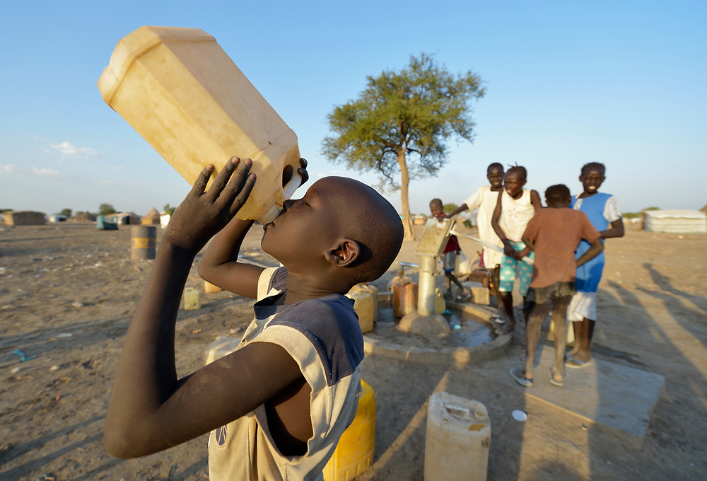 A boy enjoys water pumped from a well constructed by Caritas in a displaced persons camp in Agok, South Sudan. Tens of thousands of residents of Abyei, a contested region along the border between Sudan and South Sudan, remain displaced in Agok. Under a 2005 peace agreement, Abyei was supposed to have a referendum to decide which country it would join, but the two countries have yet to agree on who can vote. In 2011, militias aligned with Khartoum drove out most of Abyei's Dinka Ngok residents, pushing them across a river into the town of Agok. More than 40,000 Dinka Ngok have since returned to Abyei with support from Caritas South Sudan, which has drilled wells, built houses, opened clinics and provided seeds and tools for the returnees. Yet continuing insecurity means a greater number remain in Agok, where they remain dependant on Caritas and other organizations for food and other support.
