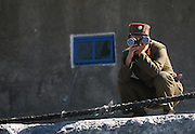 A North Korean soldier looks out at a Chinese boat with binoculars from the border town of Sunuiju October 11, 2006.  DPRK, north korea, china, dandong, border, liaoning, democratic, people's, rebiblic, of, korea, nuclear, test, rice, japan, arms, race, weapons, stalinist, communist, kin jong il