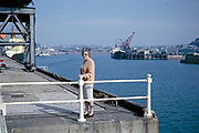 Ships in harbour at port of St Helier, Jersey, Channel Islands in 1964 woman standing on quayside