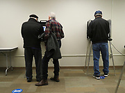A son reads the information on the voting screen to his father. By law, voters needing help may bring a person of their choice to the voting booth for assistance.