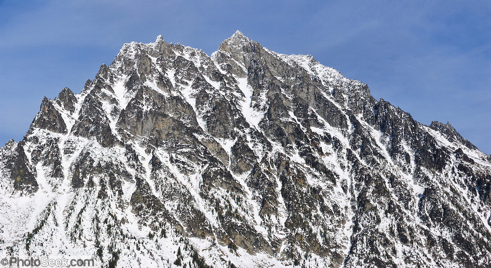 The prominent peak of Mount Stuart (9415 feet / 2870 meters) is dappled with snow in early November. It is the second highest non-volcanic peak in Washington state and tenth-highest overall. It is located in the central part of the Washington Cascades, south of Stevens Pass and east of Snoqualmie Pass in Alpine Lakes Wilderness, USA. Panorama stitched from 2 images.