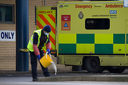 © Licensed to London News Pictures.11/01/2021, London, UK. A hospital worker prepares an ambulance for the next call out at Queen's Hospital in Romford, east London as the number of coronavirus cases surge. London Mayor Sadiq Khan has declared a major incident in London as the capital's hospitals struggle to cope with the number of patients. Photo credit: Marcin Nowak/LNP