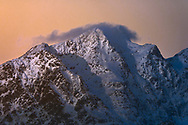 The rising sun shines onto the jagged snowcapped peaks in Lofoten islands, Norway.