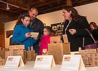 Alyssa Pepin reads about the Mill her sister Anna (in pink) made with Matt Pepin and Lisa DuBois during Elm Street School's display of mills and factories made by the 3rd grade class at the Belknap Mill on Thursday evening.  (Karen Bobotas/for the Laconia Daily Sun)