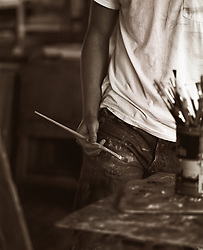detail of a man with a paint brush working in a studio