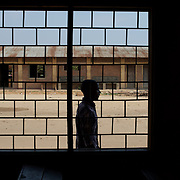 A member of Burundi's National Electoral Commission passes outside a window of a classroom that will be used as a poling station in the upcoming parliamentary elections in Cibitoke neighbourhood, Bujumbura, June 28th, 2015.