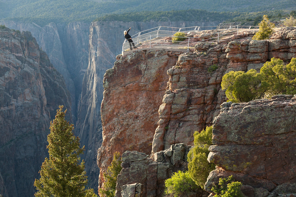 A man photographs himself at the Island Peaks View overlook in Black Canyon of the Gunnison National Park, Colorado.