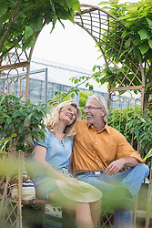 Mature couple sitting on a bench and smiling in plant nursery, Augsburg, Bavaria, Germany