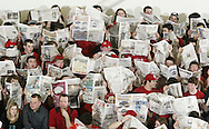 Red Hook boys' basketball fans hold up newspapers as Cornwall players are introduced before the start of the Section 9 Class A championship game at SUNY New Paltz on Friday, March 4, 2011.