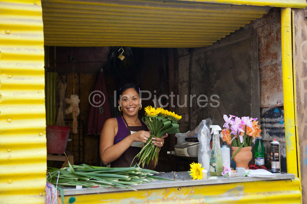 A happy Cuban woman selling flowers and smiling, yellow flowers and a yellow storefront.