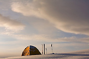 A tent, skis and poles - overflow from the Elfin Lakes Hut - against a sunrise sky in Garibaldi Provincial Park, British Columbia, Canada.