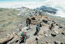 "Nov 3, 2016 - Kilimanjaro, Tanzania - Swiss-American HANS REY, German GERHARD CZERNER and Scotsman DANNY MACASKILL ride down on the crater rim from Kilimanjaro. Professional mountain bike riders Hans Rey, Danny MacAskill and Gerhard Czerner are the first to take on Africa's two highest mountains back to back on mountain bikes. On Oct 26th Rey and Czerner summit Africa's second tallest mountain, Mount Kenya's Point Lenana (4,985m/16,355ft) with their mountain bikes. On November 3rd, only one week later, together with urban trials YouTube sensation Danny MacAskill; they also summited Mount Kilimanjaro (5,895m/19,340ft), the Roof of Africa. There have only been a handful of people who have taken their bikes to either Mount Kilimanjaro or Mount Kenya in the past, but none have achieved both, one straight after the other. Others carried their bikes for the majority both up and down the mountains, while Rey (Swiss/American), MacAskill (Scottish) and Czerner (German) rode 98% of the descent. They are world renown extreme bikers and their feats will be featured in a TV documentary, magazine stories and an upcoming film about the Mountain Bike Freeride history, titled ""Nothin For Free"" produced by Freeride Entertainment. The hardest part about the trip was adjusting to the high altitude. The terrain is extremely technical and challenging, several different eco-systems are being crossed on the way, from rainforests to glaciers. It took the riders 4 days to summit and traverse Mount Kenya, and 6 days to summit and descend Mount Kilimanjaro. The National Parks plan on extending their programs to permit bike riders in the future. For those that dare, there are adventures and ultimate challenges both physically and mentally awaiting them. (Credit Image: © Martin Bissig via ZUMA Wire)"