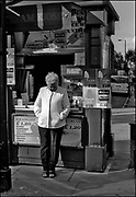 Woman rests on a candy & ice cream kiosk