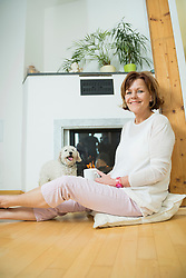 Portrait of senior woman with dog sitting in front of fireplace, smiling